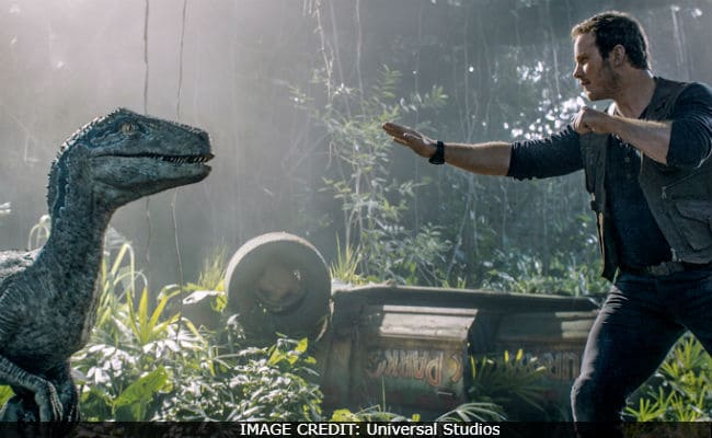 Chris Pratt holds back a raptor in Jurassic World: Fallen Kingdom.