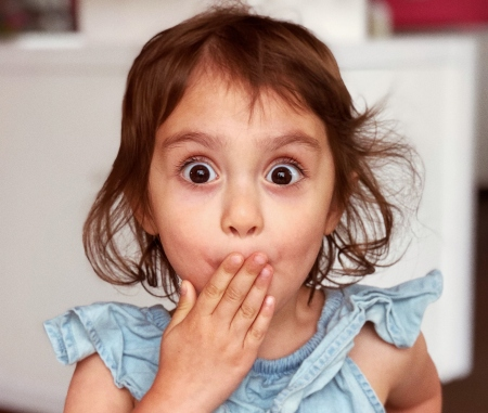 Little girl covers her mouth